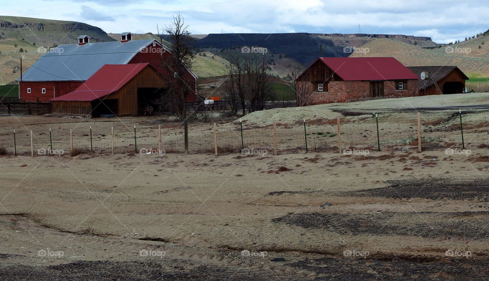 A rural country farm against the hills of Eastern Oregon on a spring day.