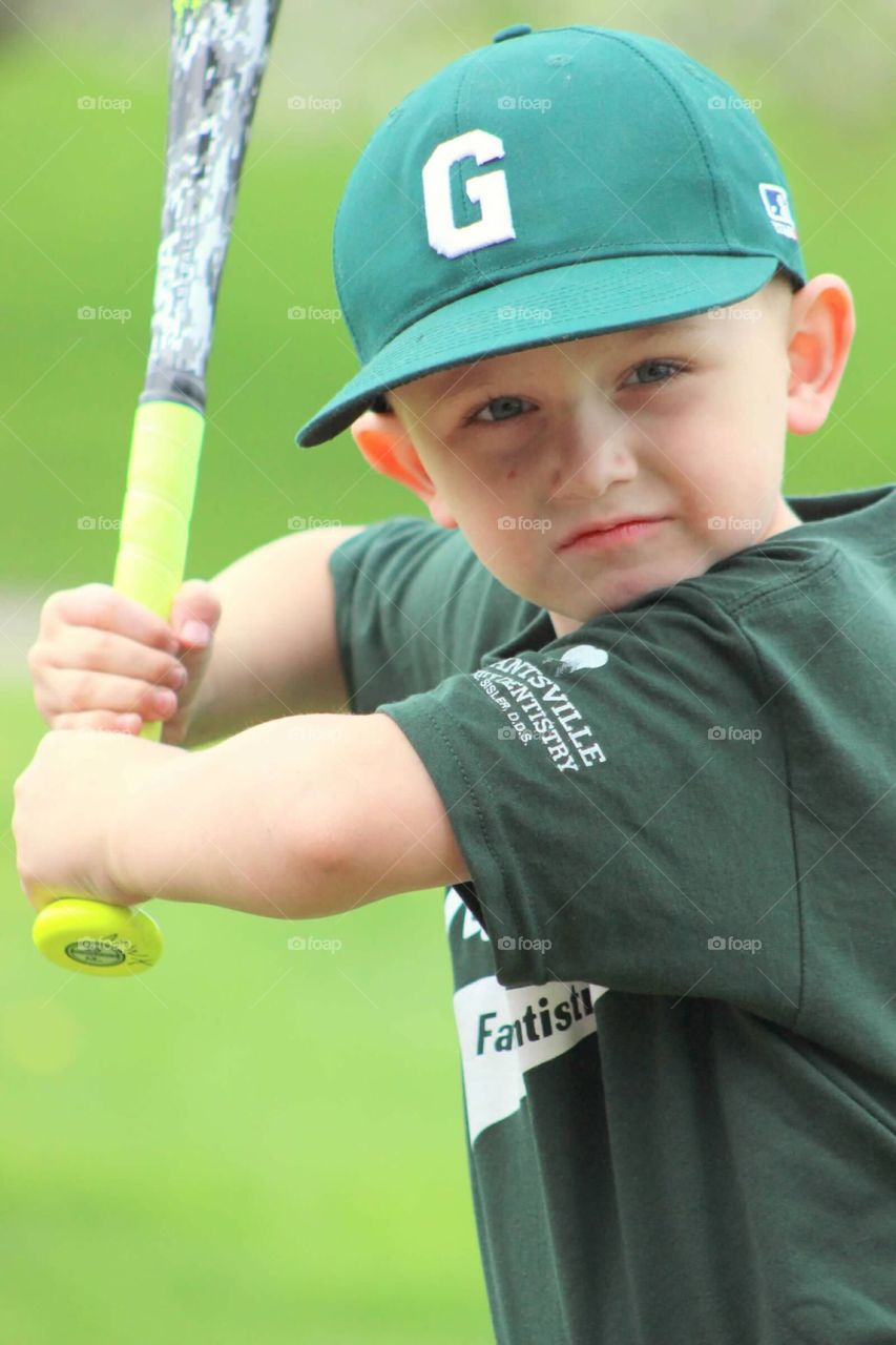 A serious look of determination and focus as he is posing for the camera in his best batting stance.