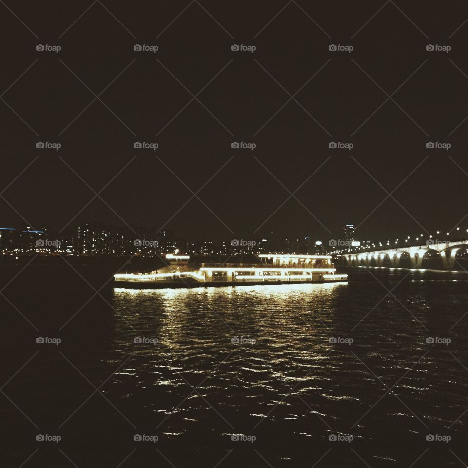 A ferry lit up at night on the Han River in Seoul, South Korea.