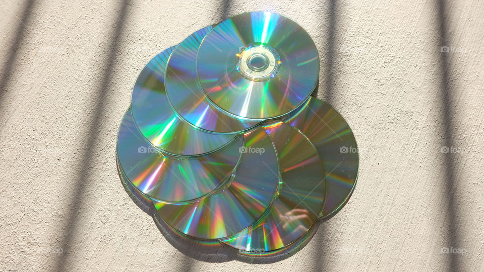 Boring grey cement background is a contrast to shiny CDs reflecting colorful lights.