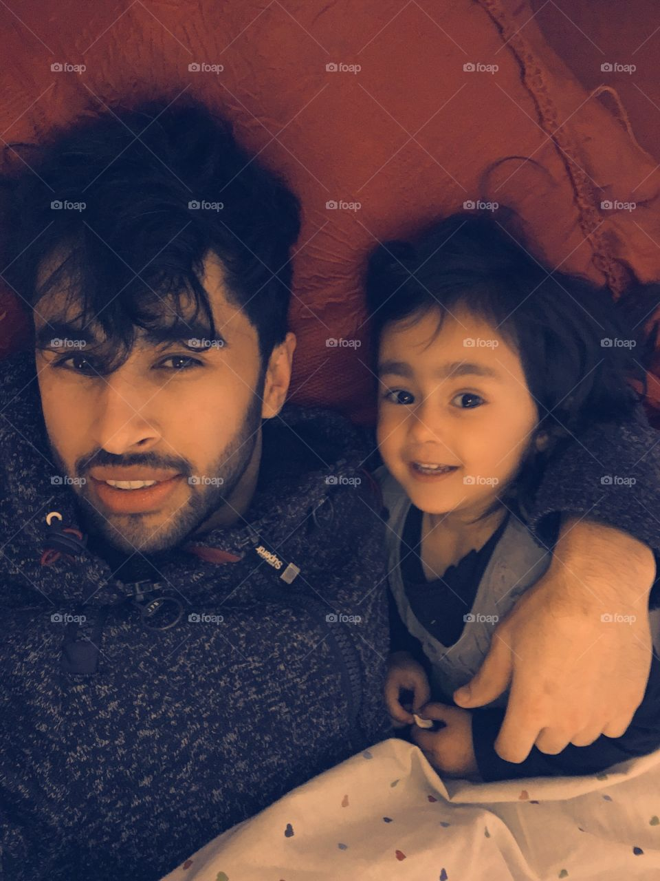 High angle view of father and daughter lying on bed