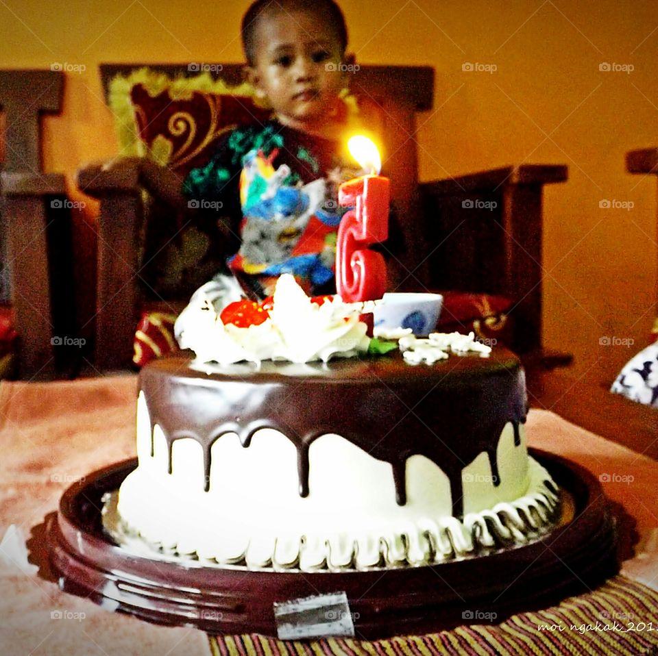 Close-up of birthday cake with illuminated candle