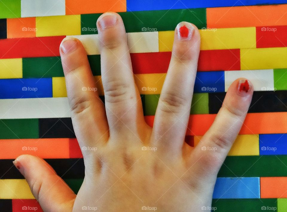 Helping Hand. Hand On Colorful Building Blocks