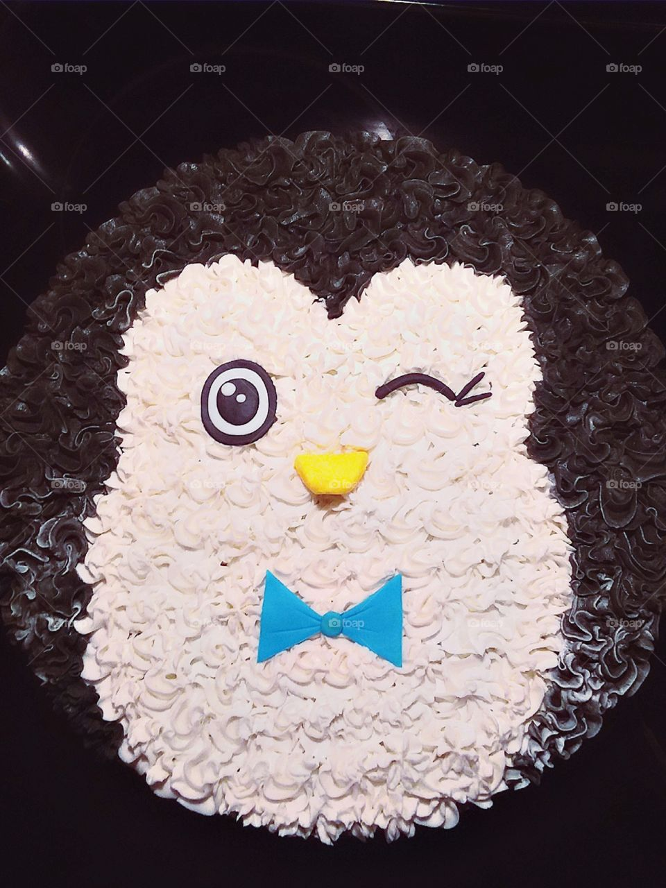 Stunning winter cookie cake decorated like a penguin winking and wearing a bowtie