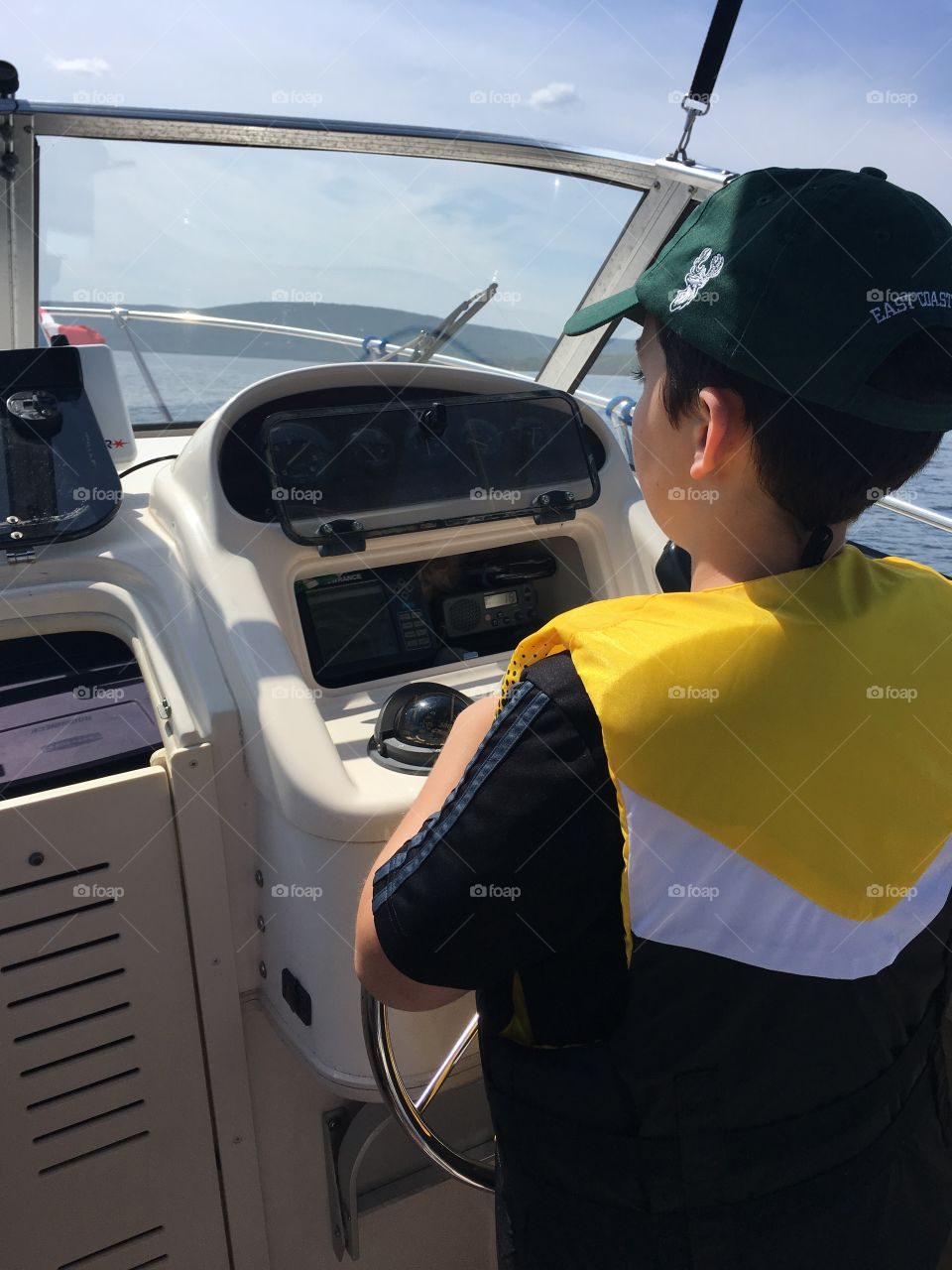 Young boy learning to drive a boat wearing a yellow life jacket and green ball cap.