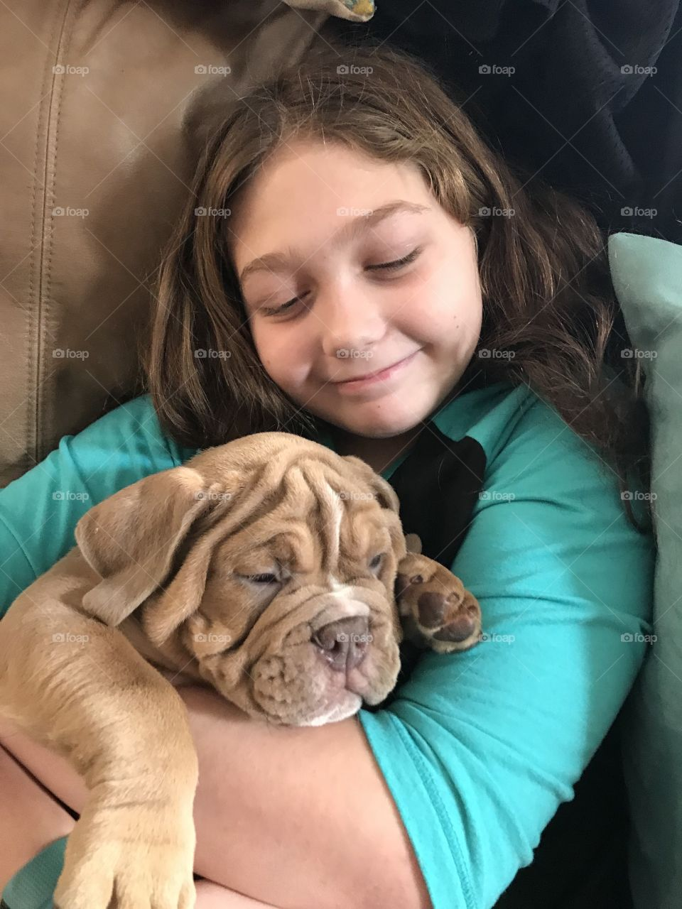A little girl happily loving her new bulldog puppy.
