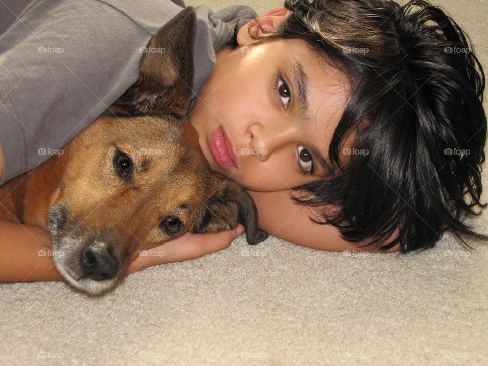 Close-up of boy with dog at home