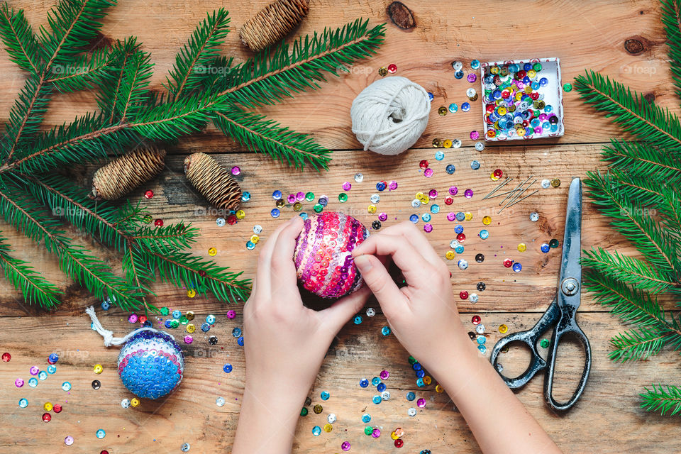 Girl making Christmas decoration by pinning the sequins onto the ball