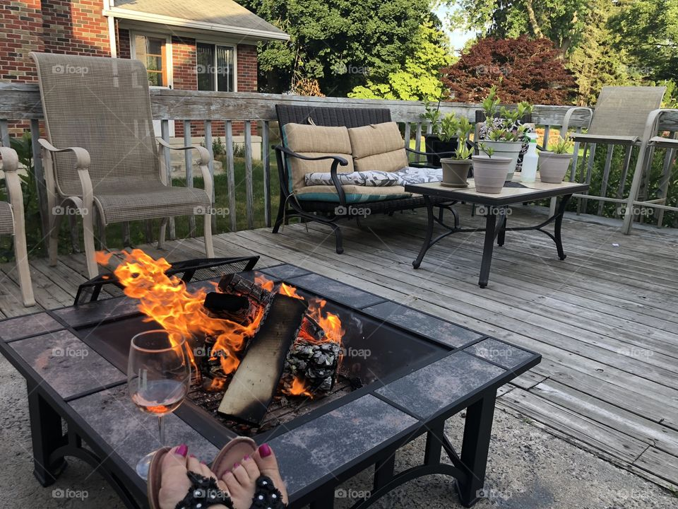 Sitting on the deck in front of a fire pit drinking wine