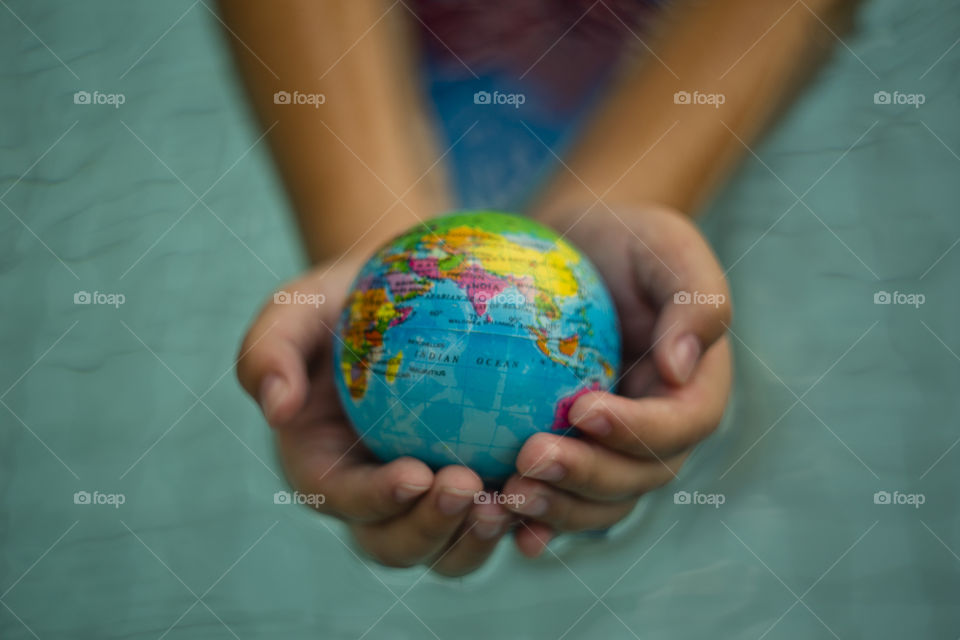 overhead looking down on hands holding world sphere Asia continent