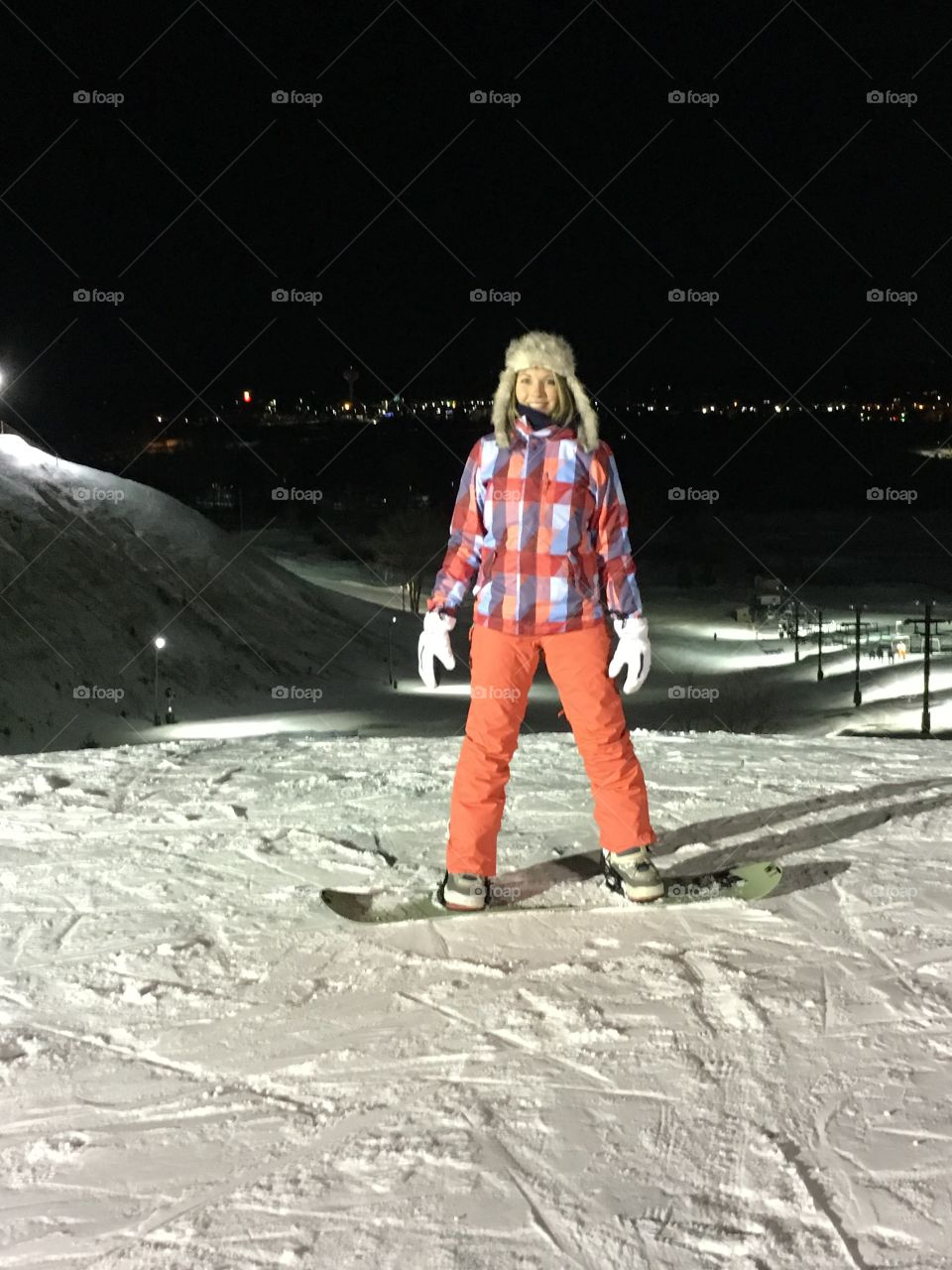 Happy woman rides snowboard