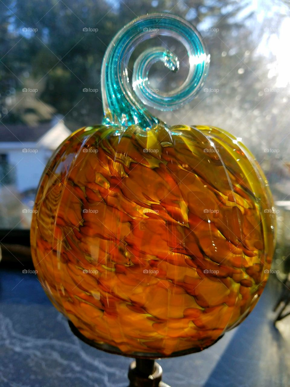 Handblown glass pumpkin seen with sun shining through, showing all colors of glass used. Stem is blue and spiral shape.