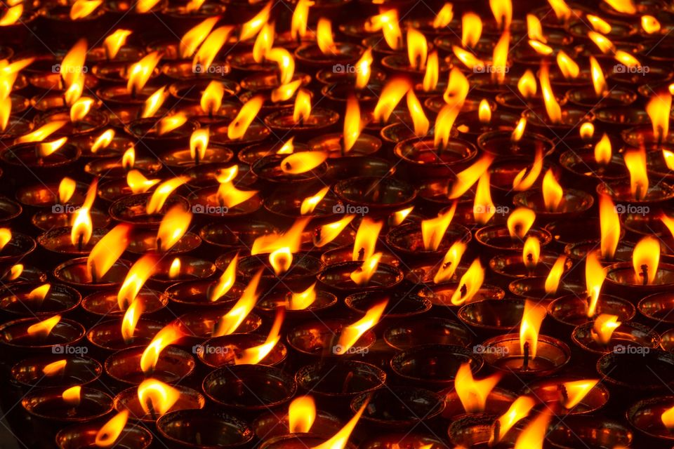 Photo full of burning candles. Frame filled with burning candles. Yellow orange flame. Cup candles
