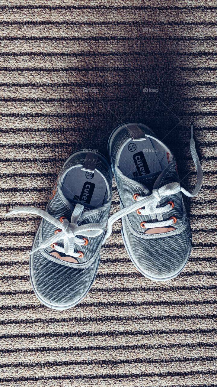 two year baby boy shoes on carpet