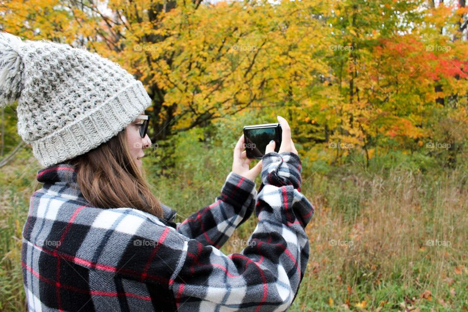 Young woman taking a photo of trees in the fall