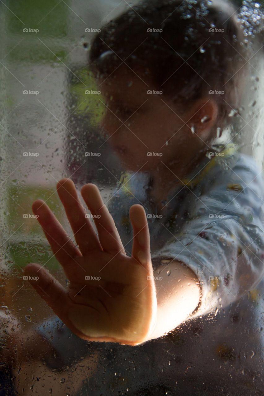 sad portrait of a boy through wet glass
