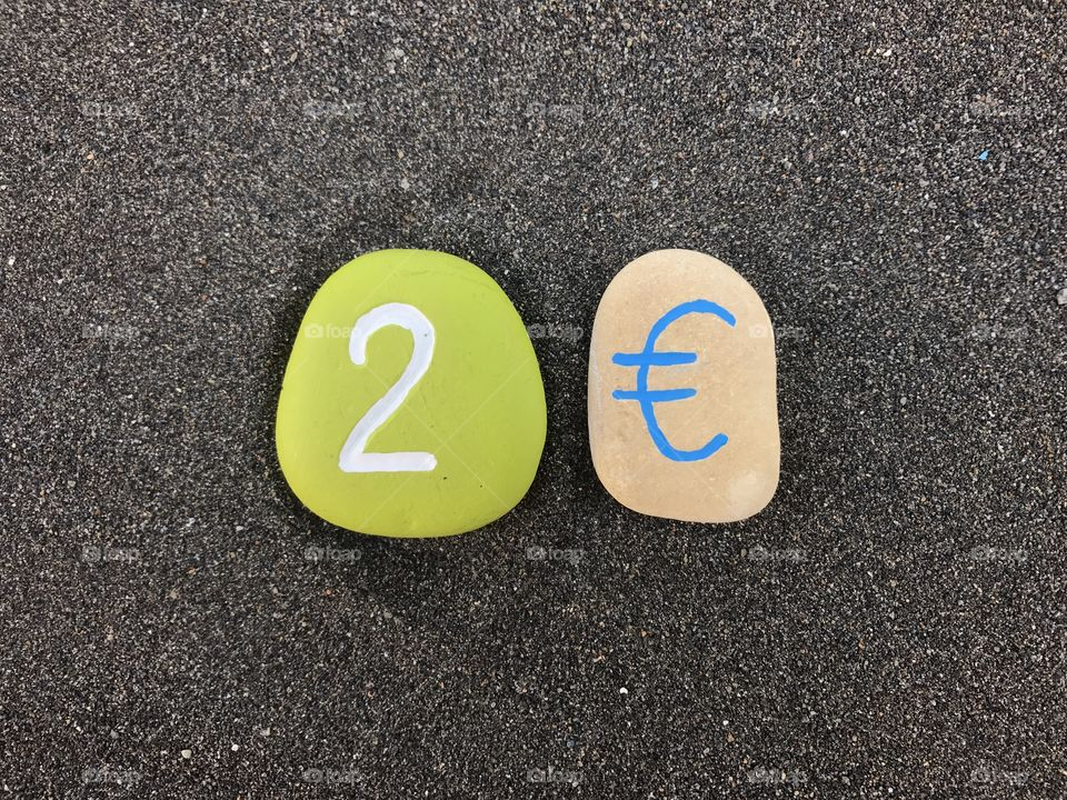 2 Euro with colored stones over black volcanic sand