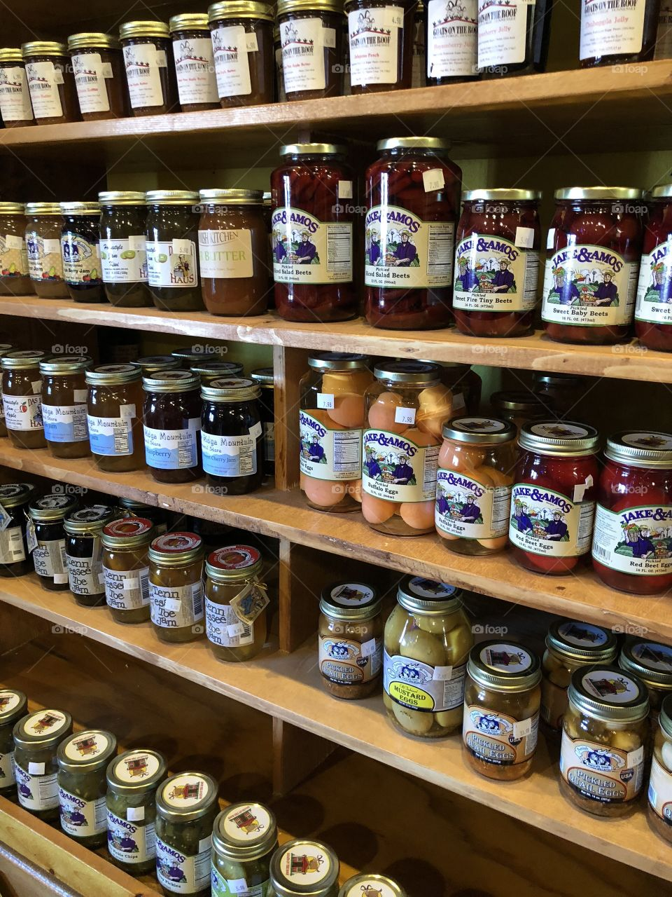 Many jars filled with preserves on shelves in an old store.