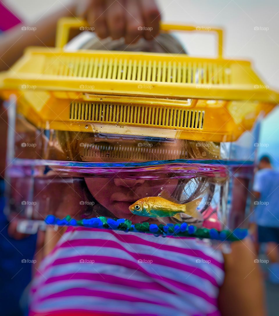 A little girl holding aquarium in front of her face