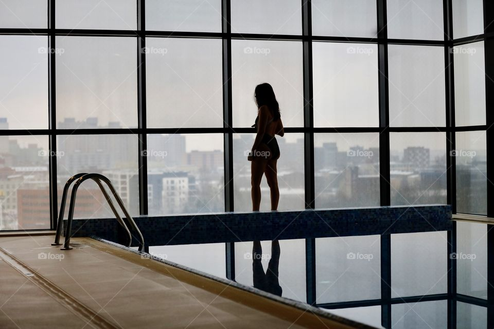 A woman in the pool watches the panorama of the city