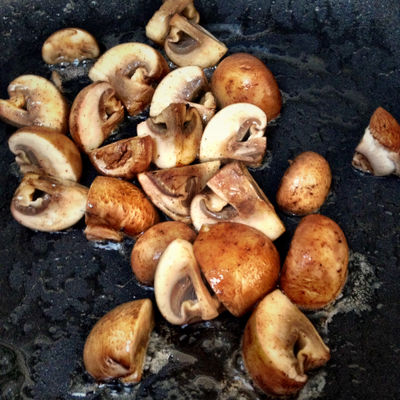 Small Portobello Mushrooms Cooking In A Frying Pan Skillet
