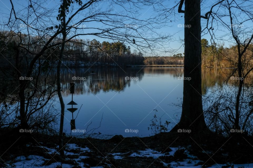 The waning sunshine strikes the opposite shore, with a silhouette and reflection of a wood duck box in the millpond at Yates Mill County Park in Raleigh North Carolina.
