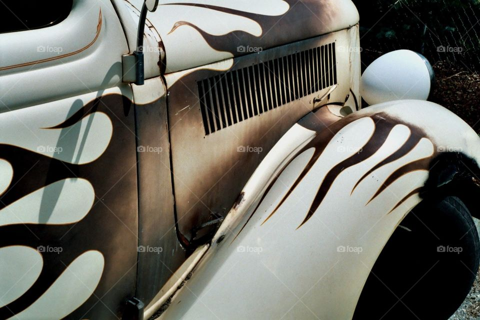 This is a photo of a classic oldsmobile that is white with brown flames painted on it.