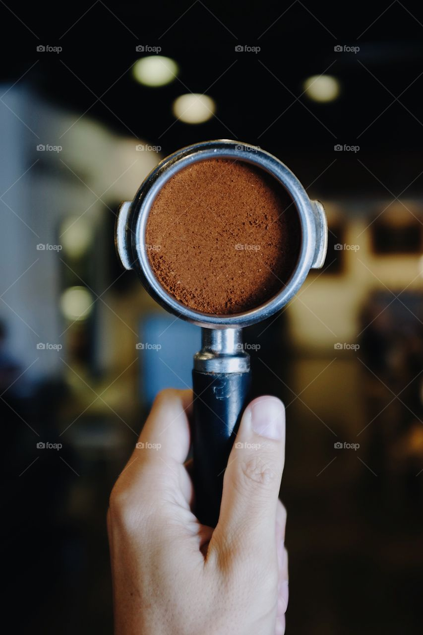 Hand holding a portafilter filled with espresso coffee with a bokeh background inside of a coffee shop.