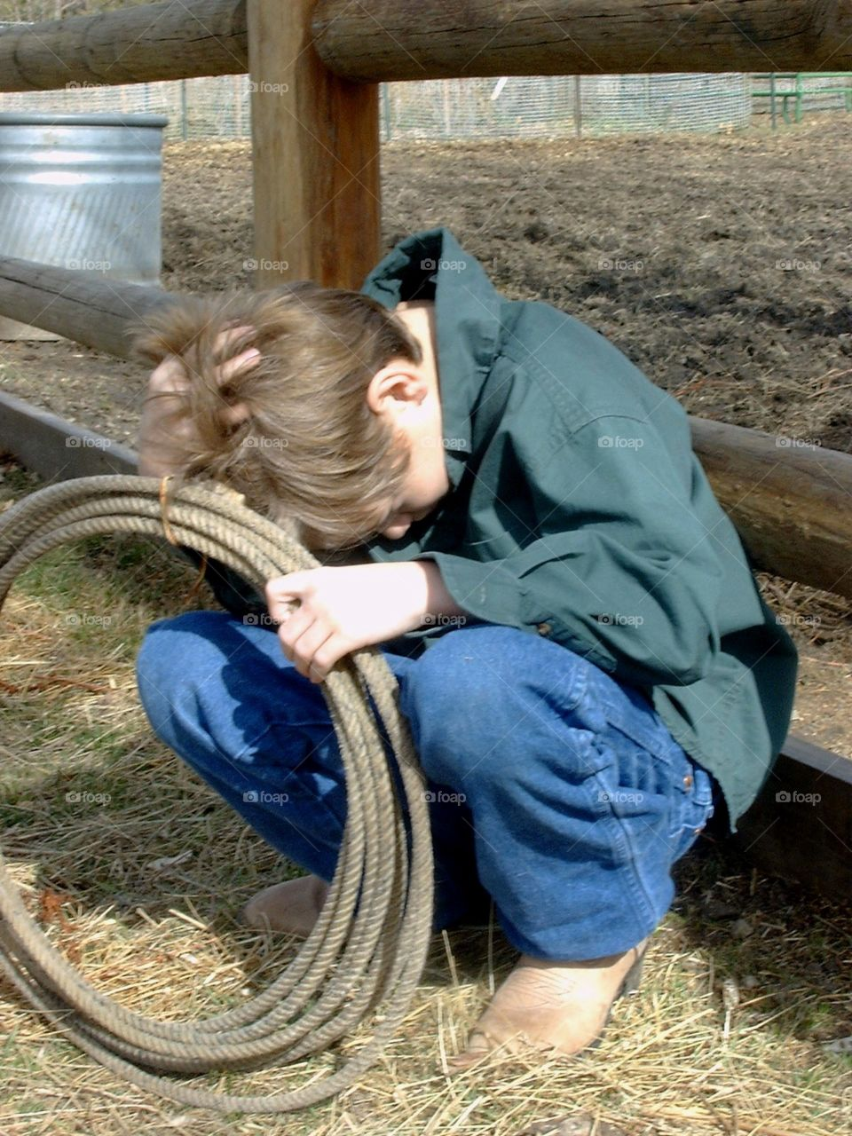 This is a photo of a young boy sitting outside of a horse pen, with a lasso in his hand and his head down looking discouraged.