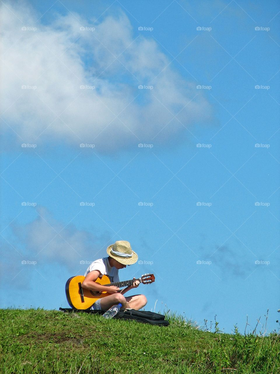 A young boy plays his guitar on a hillside with a beautiful blue sky overhead.
