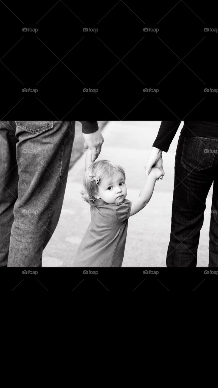 Little girl walking with mom and dad in Black and white