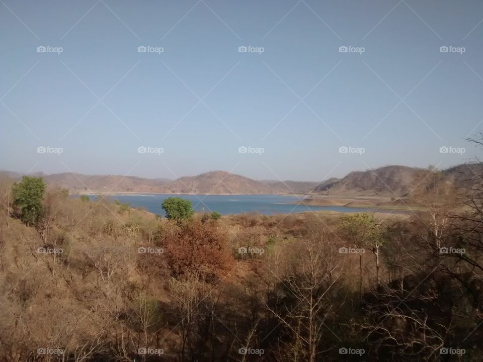 around mountain with forest and big water storage for dam