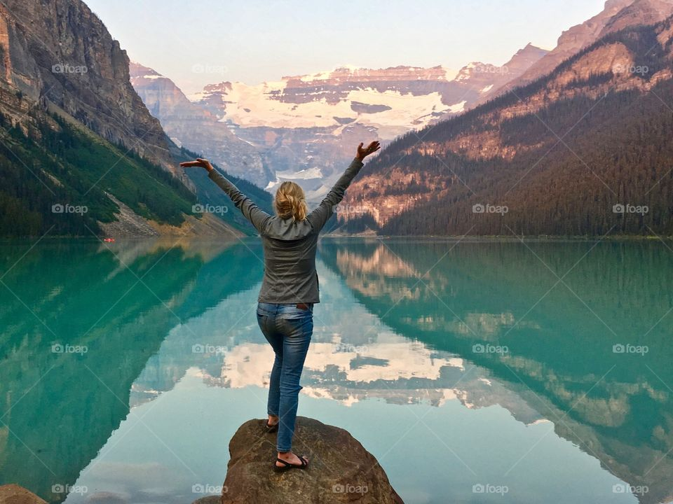 Woman standing on large rock in front of beautiful Lake Louise in Canada's Rocky Mountains with arms outstretched in praise and wonder