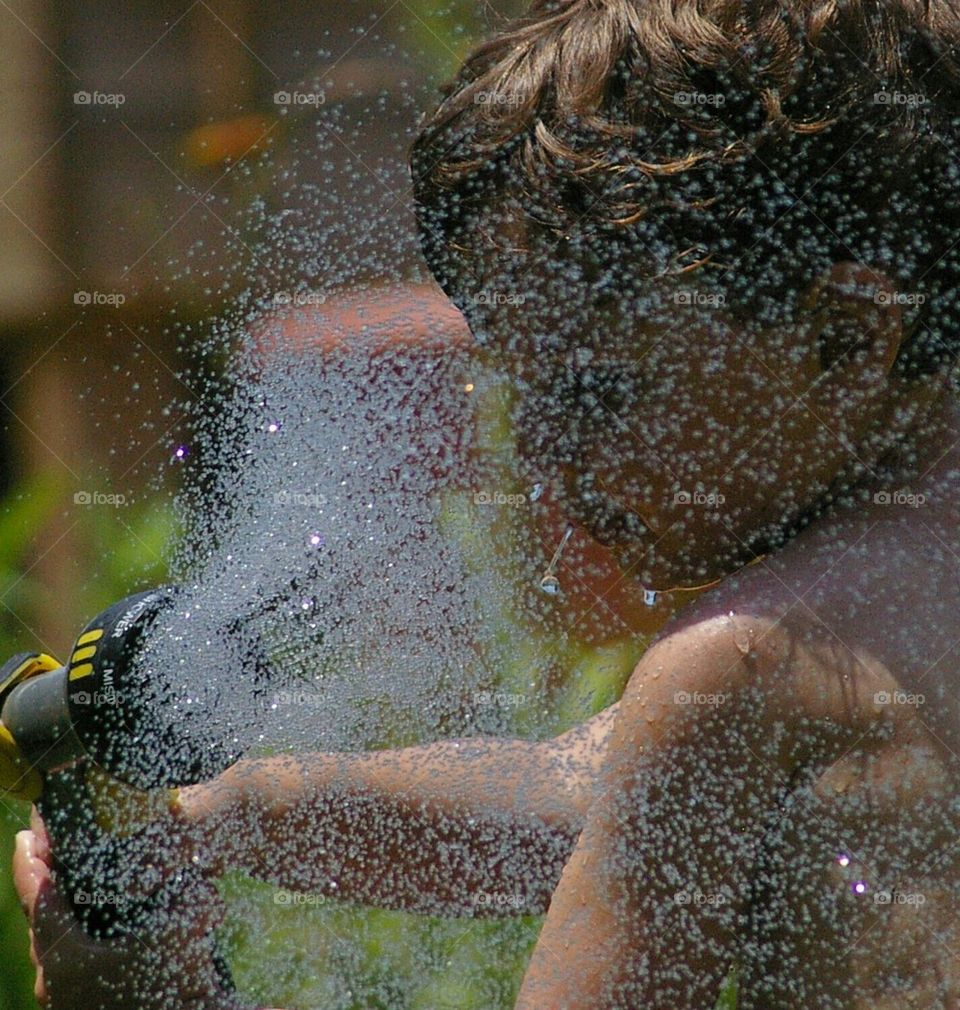boy hoses himself in the face