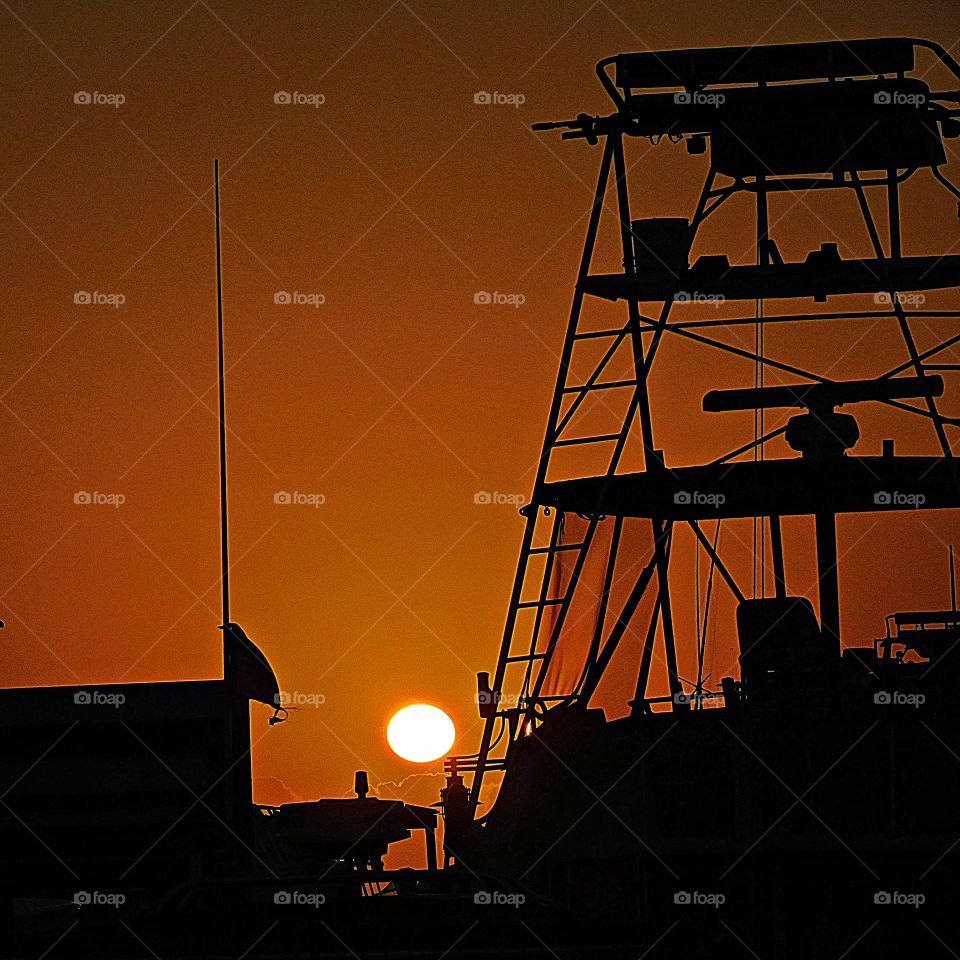 Sunrise, sunset and the moon - The orange sun rises over the silent fishing vessel