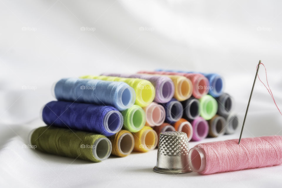 Different colored spools of thread with a fingernail on a white background