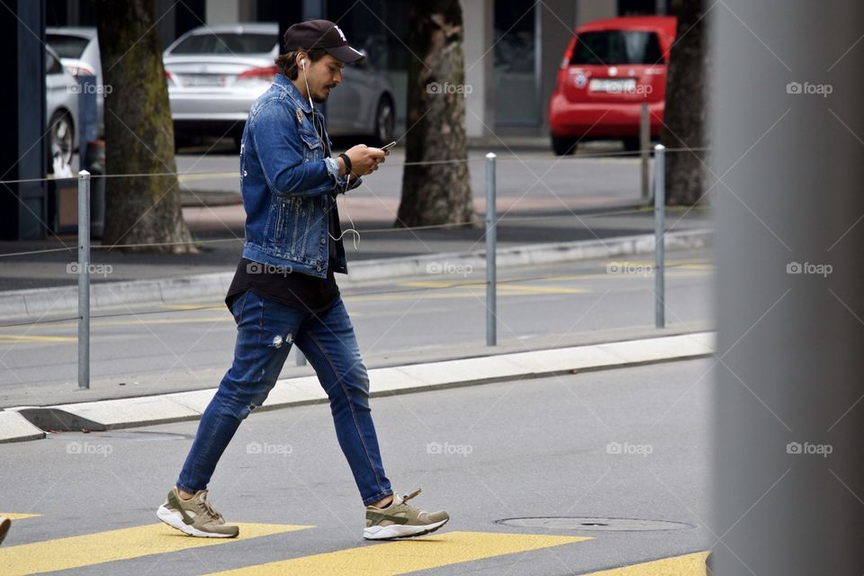 Street Photography.Man texting while crossing the road.