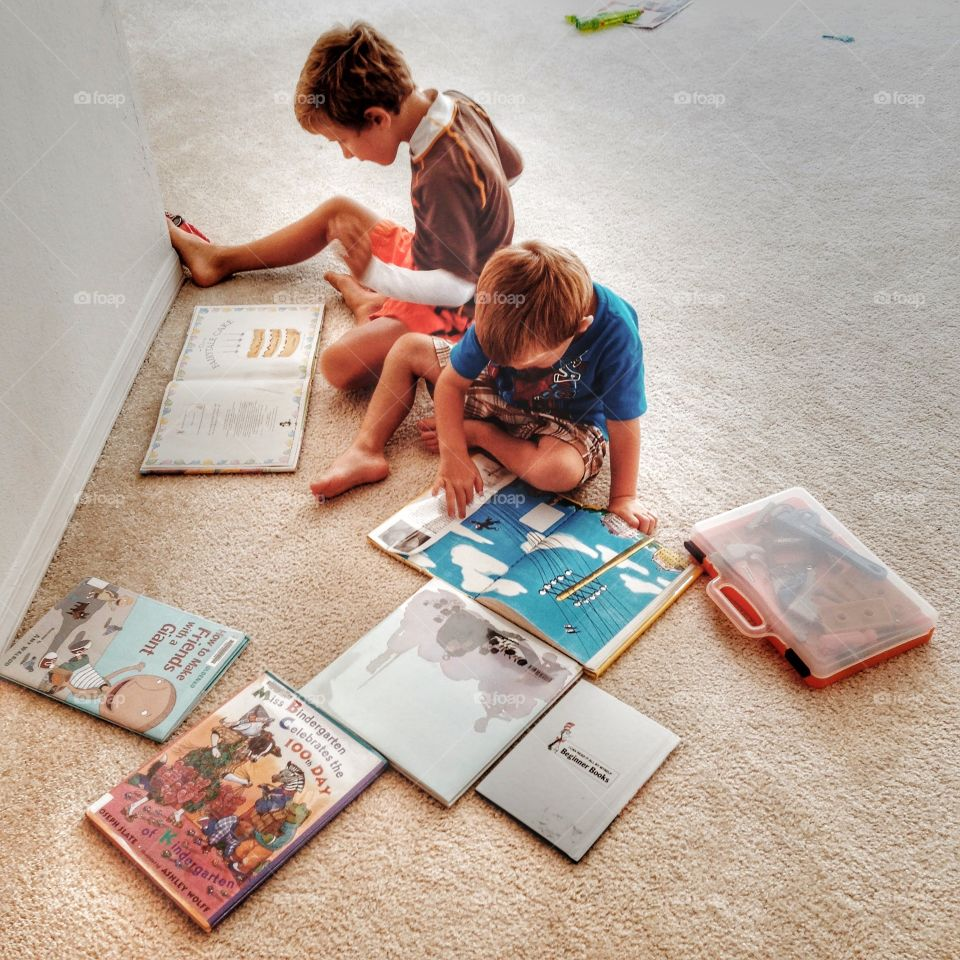 Boys reading books together. The books are scattered on the floor. The boys are very focused on their reading
