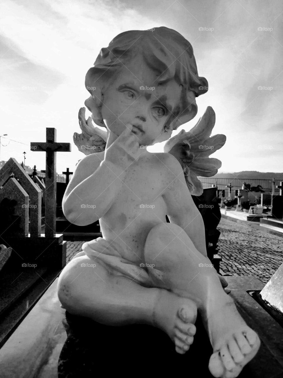 Black and white photograph of a stone angel in the cemetery