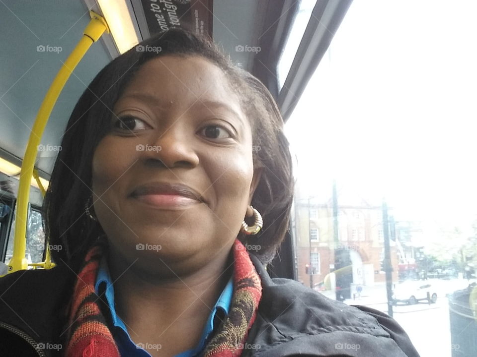 Woman on a London bus wearing a coat and scarf