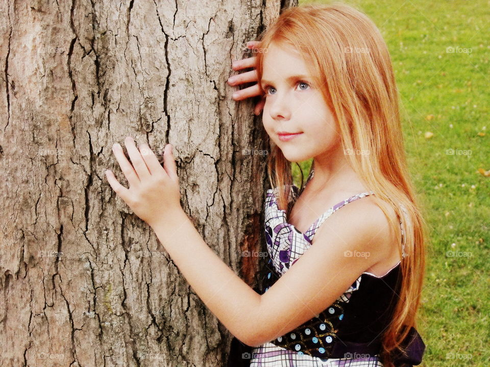 Day dreaming girl on tree trunk