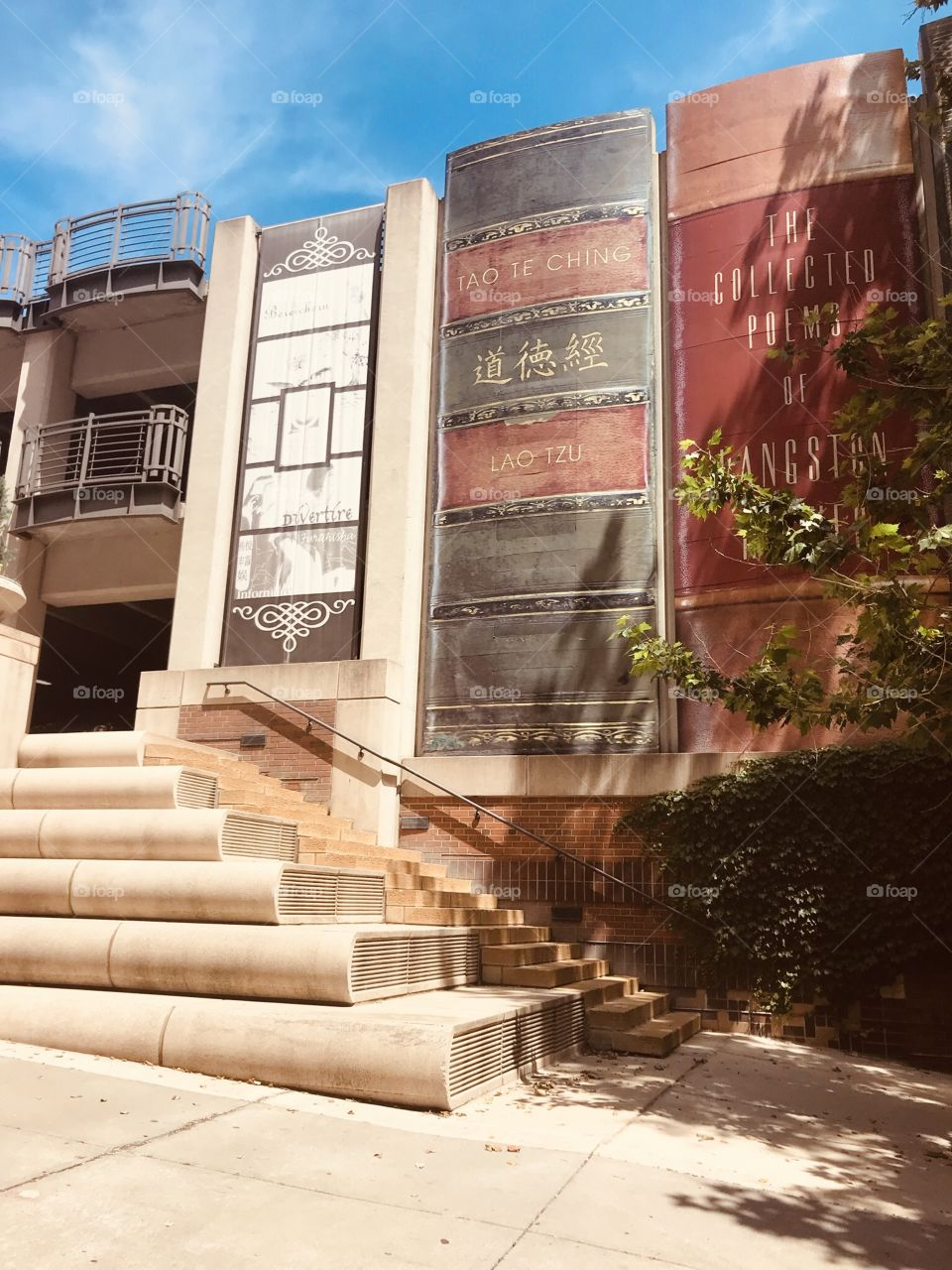 Gorgeous wall mural on library in Kansas City, MO of books lined up and the building is even complete with books stacked on each other for steps!!