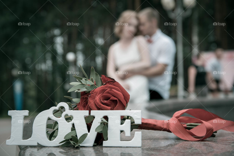 Love text on table with rose flowers