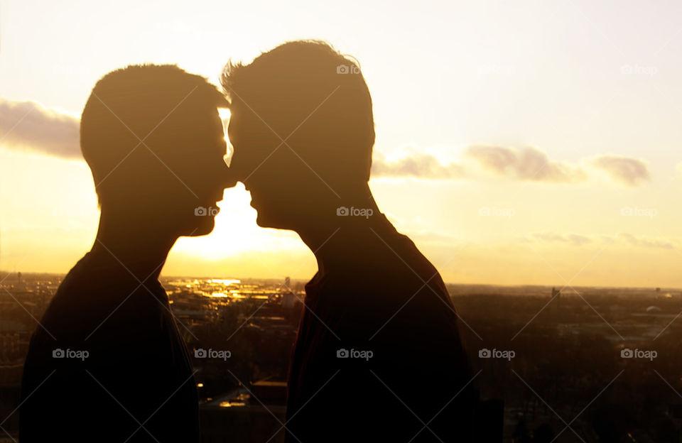 SUNSET MEN KISSING