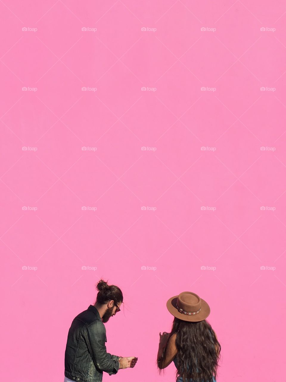Two people and a pink wall.