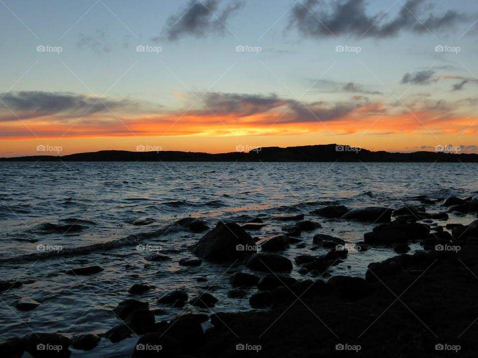 Silhouette of stones at beach during sunset