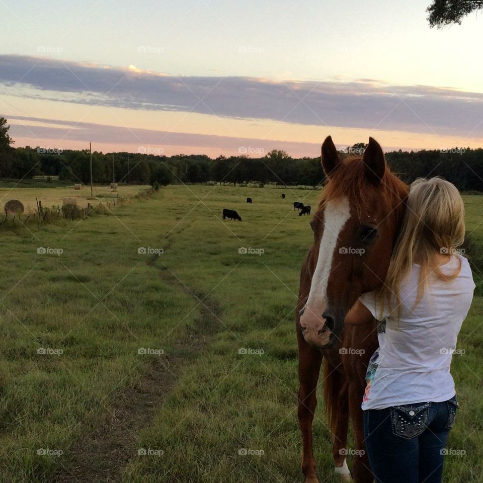 And girl and her horse at sunset