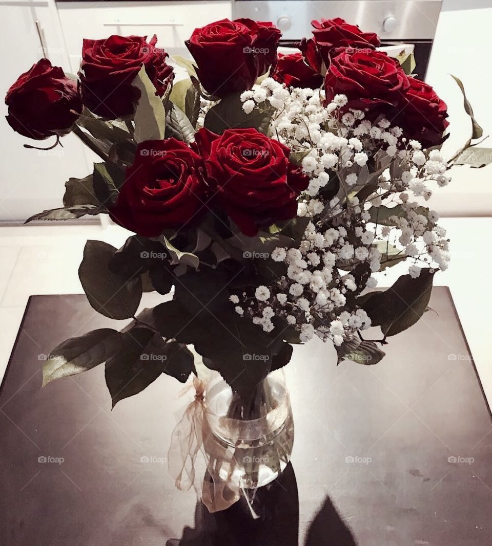 A beautiful bunch of red roses in a vase with a golden bow and white blossom