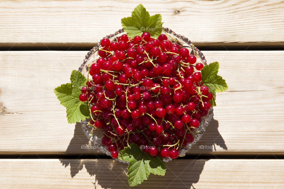 Red currant on glass dish placed on wood, from above