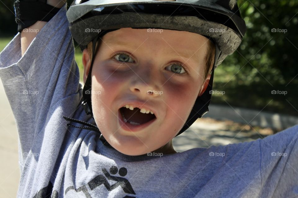 Darling photo of young boy excited to get his blades, elbow pads and helmet back on for the summer!!
